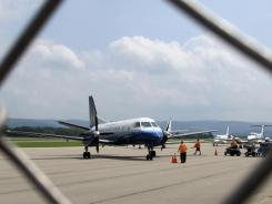 Ground crew works on a flight at the Morgantown Municipal Airport in Morgantown, W.Va., on Tuesday.