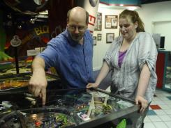 Rob Wintler-Cox and daugher, Zoe, of Gaithersburg, Md., play on the Creature From the Black Lagoon machine at the National Pinball Museum in D.C.