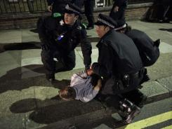 Police officers restrain a man Wednesday in Eltham, London.