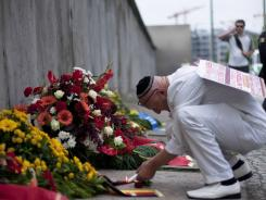 Achim von Almrich lights a candle at the Berlin Wall Memorial at Bernauer Strasse  in Berlin.