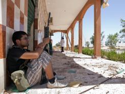 A Libyan rebel rests near the frontline outside Zawiya in western Libya on Saturday.
