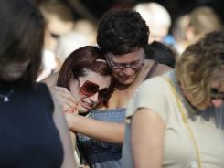 Friends of Alina Bigjohny comfort each other during a memorial service at the Indiana State Fair in Indianapolis on Monday,