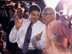 Republican presidential candidate Rick Perry applauds for fellow candidate Michele Bachmann as she takes the stage in Waterloo, Iowa, on Sunday.