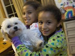 Victoria Benson, 8, left, and her sister, Olivia, 7, at the happy reunion of their Maltese, Caesar, at their Clio, Michigan home Saturday.