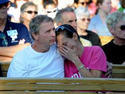 Randy Byrd, brother of accident victim Nathan Byrd, hugs his wife Sandy during a memorial service Monday morning at the Energy Armor Freestage of the Indiana State Fair.