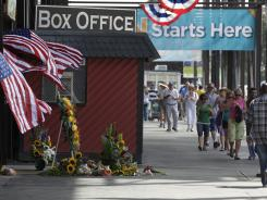 Patrons walk past a memorial in front of the grandstand at the Indiana State Fair on Monday.