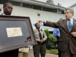 Los Angeles Sheriff lead detective Clarence Williams, left,  and Los Angeles County sheriff's spokesman Steve Whitmore, right, display the recovered $250,000 quill pen Rembrandt.