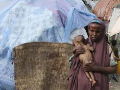 A Somali woman holds her malnourished child in a refugee camp Wednesday in Mogadishu.