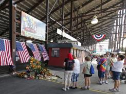 Patrons walk past a memorial in front of the Grandstand at the Indiana State Fair on Tuesday.