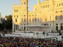 Pilgrims attend the inaugural Mass of the World Youth Day festival Tuesday at Cibeles square in Madrid.