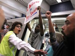 A Bay Area Rapid Transit employee scuffles with demonstrators trying to keep a train from leaving a station.