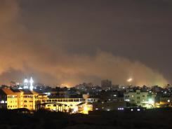 A plume of smoke rises above Gaza City during Israeli air strikes on Thursday.