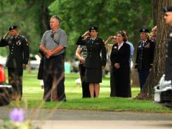Military and civilians observe the funeral procession  of Chief Warrant Officer David R. Carter on Friday.