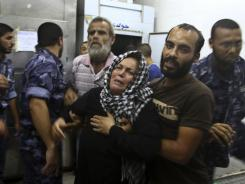 The mother of Islamic Jihad militant  Anwar Isleem, reacts after seeing his body after an Israeli airstrike east of Bureij, at the morgue of Aqsa hospital in Deir Al Balah, central Gaza, Aug. 19.