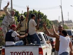 Residents greet advancing rebel fighters on the outskirts of Tripoli on Monday.