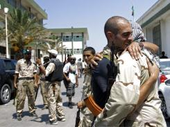 Libyan rebel fighters embrace Monday at the former female military base in Tripoli.