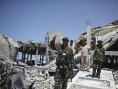 Rebel fighters flash the V-for-victory sign on Aug. 15 in Brega, Libya, at the site of  a  communications center reportedly bombed by NATO planes.