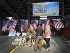 Fairgoers stop Sunday at the makeshift memorial for the victims of a stage that collapsed just before Sugarland was to perform at  the Indiana State Fair in Indianapolis.