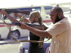 Libyan rebel fighters shoot toward pro-Gadhafi forces during fighting in downtown Tripoli on Monday.