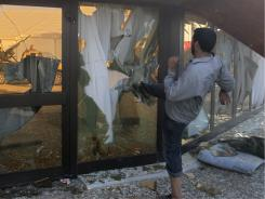 A rebel fighter breaks the glass of Gadhafi's tent after Libyan rebels stormed Gadhafi's main military compound in Tripoli on Tuesday.