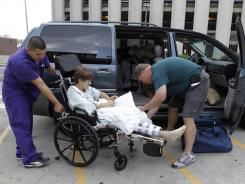 Tim Brunn, right, helps his son Josh into their van after he was released from Riley Hospital for Children in Indianapolis. Josh, along with his mom, Karen, were injured when a stage collapsed at the Indiana State Fair last week. Irwing Rivera, left, helps the Brunns.