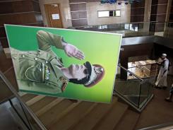 People carry a portrait of Moammar Gadhafi inside a hotel in Tripoli, Libya.