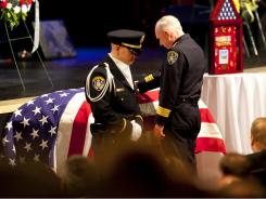 Police Chief William Lansdowne at the casket of Officer Jeremy Henwood, who was shot in an unprovoked attack during a routine police patrol in San Diego.