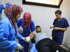 Wael Abdu Salam is treated after a gelatin bomb exploded in his hand, costing him three fingers.