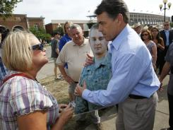 Republican presidential candidate Rick Perry is approached in Des Moines, Iowa, last week by Patty Benal, with a cut out of her son  serving in Afghanistan.