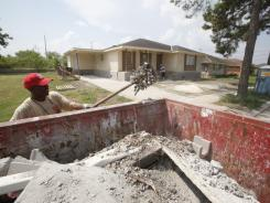 Contract worker Willie Yarls shovels up gravel from a home on Grant Street in New Orleans East, where progress remains slow-going,