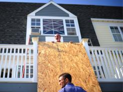 Michael Curcio sets up wood boards to protect his house at Rockway Beach, New York.