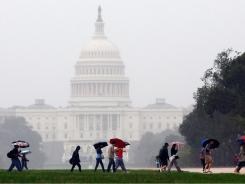 Tourists struggle against the wind and rain while visiting the nation's capital in advance of the arrival of Hurricane Irene on August 27 in Washington.