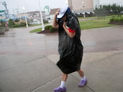 Diane Casey, of Virginia Beach, Va., flees the boardwalk in advance of Hurricane Irene on Saturday morning.
