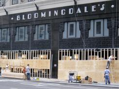 Workers install boards to protect the front windows of Bloomingdale's in preparation for Hurricane Irene's arrival Saturday morning in New York.