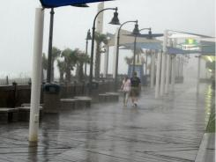 A man and woman walk along the boardwalk in downtown Myrtle Beach, S.C., in rain spawned by Hurricane Irene on Friday.
