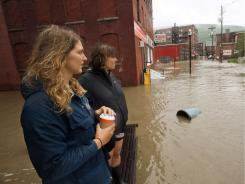 Paige Martin, far left, and Anna Knecht Schwarzer watch from a bench at the Transit Center as the Whetstone Brook floods downtown Brattleboro, Vt. on Sunday.