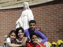 Heather Coffy at St. Monica School with her children, Alanna Marshall, 8, Delano Coffy, 15, and Darius Coffy.