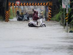 Scooter riders push their motorbikes through floodwaters caused by Typhoon Nanmadol in Linbian, Taiwan.
