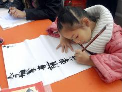A girl writes traditional Chinese calligraphy with a hair pencil. China's Ministry of Education has ordered all elementary schools to hold a weekly calligraphy class for grades 3 to 6.