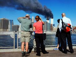 Sept. 11, 2001: Pedestrians on the waterfront in Brooklyn, New York, look across the East River to the burning World Trade Center towers.