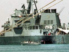 In this Oct. 20, 2000, file photo, a small boat guards the USS Cole in Aden, Yemen. A hidden network of American companies headed by a prominent defense contractor played a central role in the CIA's secret post-9/11 airlift that whisked captured terror suspects and their American minders to overseas prisons.