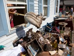 A volunteer removes debris from an office Wednesday that was flooded in Tropical Storm Irene.
