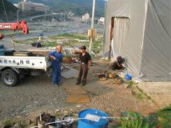 Overlooking the tsunami-wrecked downtown of Onagawa, northeast Japan, boat repairmen Motomu Endo, left, and Yohito Sasaki, center, share a joke outside the tent that has replaced their workshop.