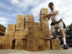 Volunteer Bill Lafferty unloads emergency food at an elementary school in Killington, Vt., on Wednesday. Some communities have been completely isolated because of the flooding caused by Tropical Strom Irene.
