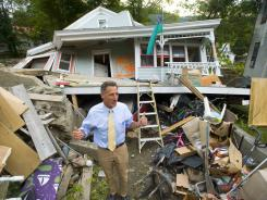 Vermont Gov. Peter Shumlin surveys the damage to a resident's house Wednesday in Rochester, Vt.