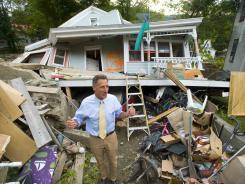 Vermont Gov. Peter Shumlin surveys the damage to a resident's house Wednesday in Rochester, Vt.