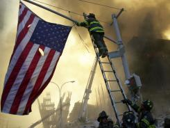 Capt. Michael Dugan hangs an American flag from a light pole in front of what is left of the World Trade Center after it was destroyed in the September 11 attacks.