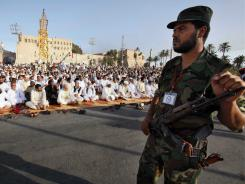 A Libyan rebel stands guard as worshipers gather for the morning Eid prayer marking the end of Ramadan on Wednesday in Tripoli.