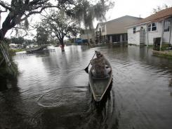 Ernie Adams paddles his pirogue to his house in floodwaters of Tropical Storm Lee in Jean Lafitte, just outside New Orleans.