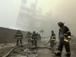 With the skeleton of the World Trade Center twin towers in the background, New York City firefighters work amid debris on Cortlandt Street on Sept. 11, 2001.